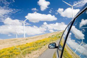 Car driving by wind farm